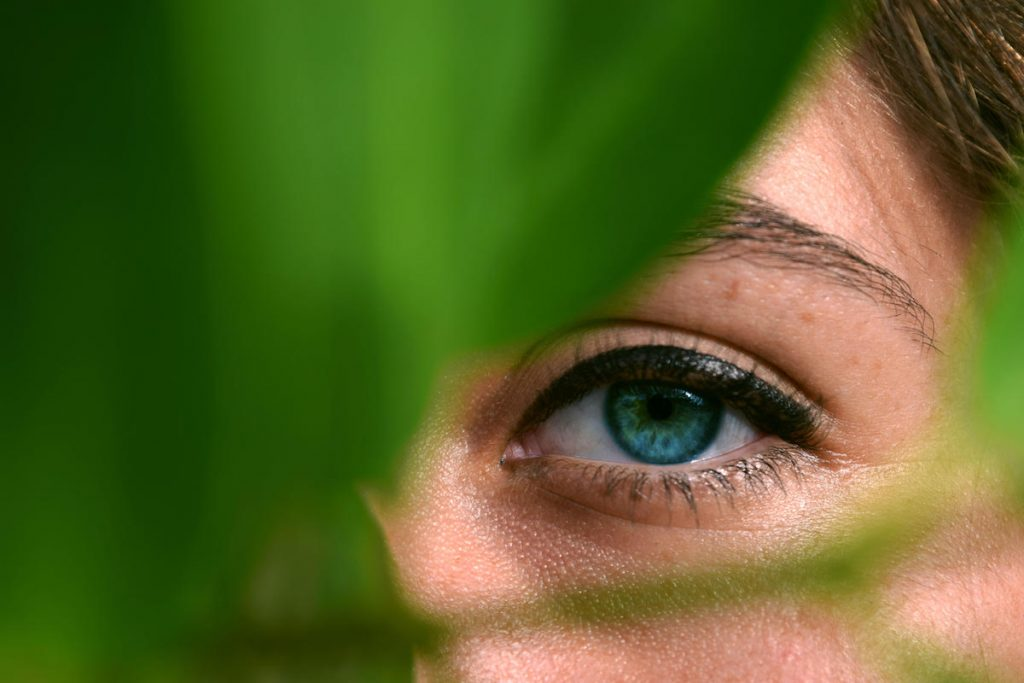 Greenwashing featured image of a girl behind a leaf